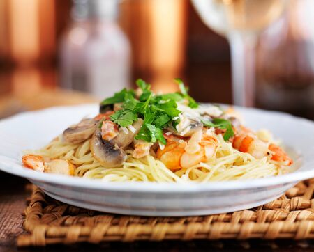 angel hair italian shrimp pasta in champagne sauce with parsley and mushrooms Archivio Fotografico
