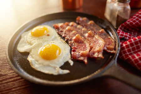breakfast eggs: fried bacon and eggs in iron skillet Stock Photo