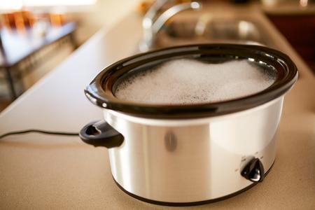 低熱キッチン ハックにせっけん水にスロークッカーを浸漬 写真素材