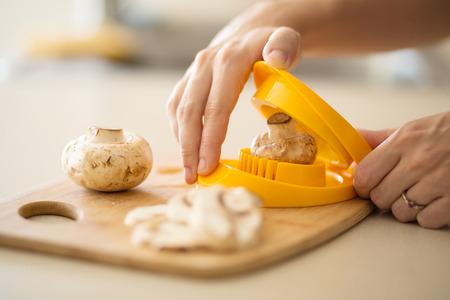 hack: mushrooms being put into egg slicer kitchen hack Stock Photo