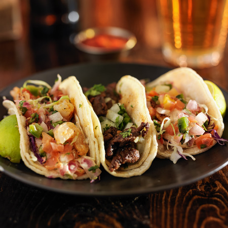 three different mexican street tacos with shrimp, steak, and fish