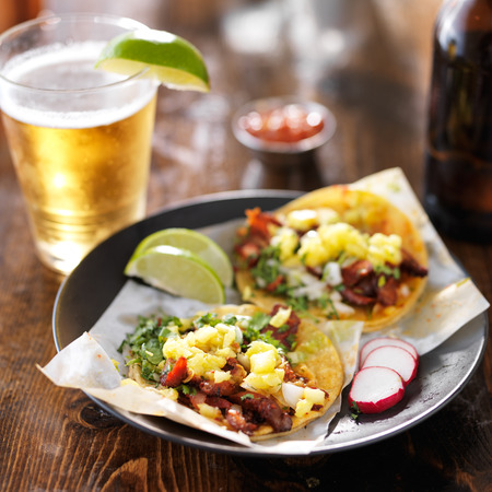 food and drink: mexican al pastor tacos in yellow corn tortillas with beer Stock Photo