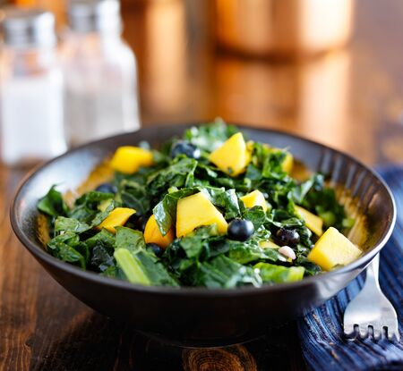 bowl of healthy blueberry mango and kale salad