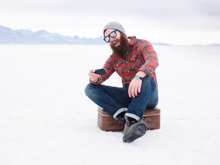 suit case: beard hipster with smart phone and suit case in the salt flats looking for directions