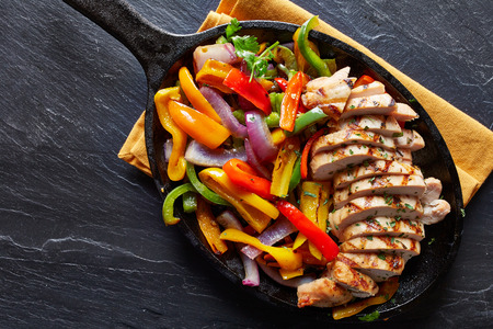 mexican grilled chicken fajitas in iron skillet shot from overhead on slate Zdjęcie Seryjne - 44182255