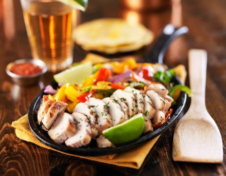 trompo de madera: pollo a la parrilla mexicana comida sartén fajita sobre mesa de madera con la cerveza en el fondo Foto de archivo