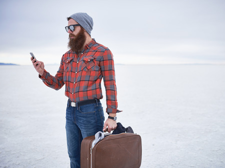 desolate: lone hipster with awesome beard using smart phone in desolate salt flats Stock Photo