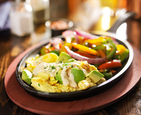 scrambled eggs: mexican fajita scrambled eggs in iron skillet with cream fresca, bell pepers, avocado and onion