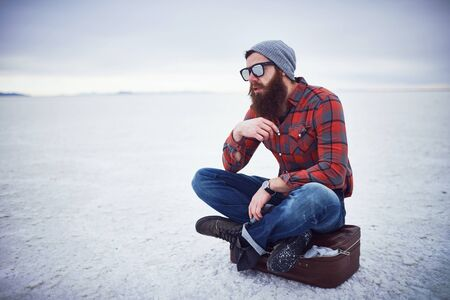 stroking: pensive contemplative hipster stroking awesome manly beard sitting on retro suitcase in salt flats all alone