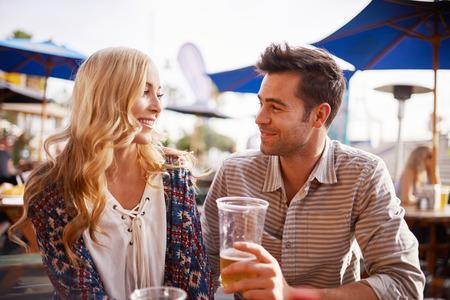 一緒にビーチ側屋外パブやバーでビールを飲むカップル