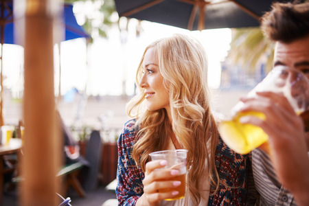 romantic beach: woman with her boyfriend enjoying drinking a beer at outdoor beach side bar or pub
