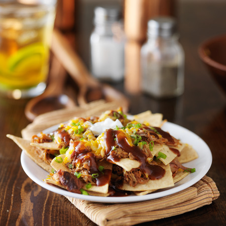 barbecue pulled pork nachos with sourcream, green onions and melted cheese