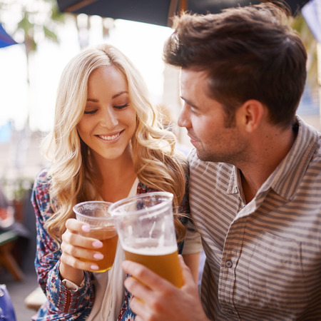 bars: romantic couple drinking beer in outdoor pub or bar making a toast Stock Photo