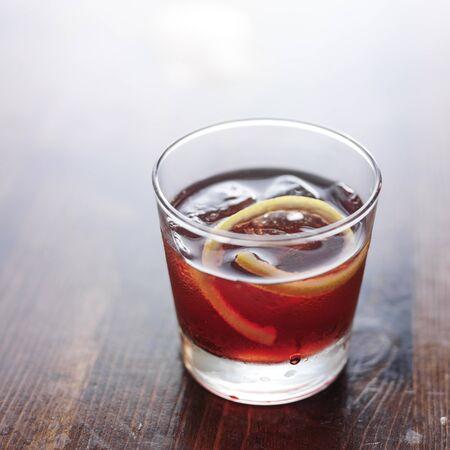 dark red: sazerac cocktail on wooden bar table top