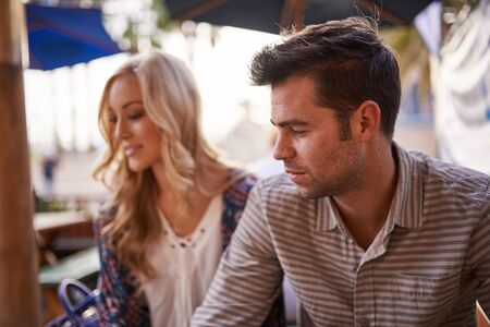 contemplative man with girlfriend in background