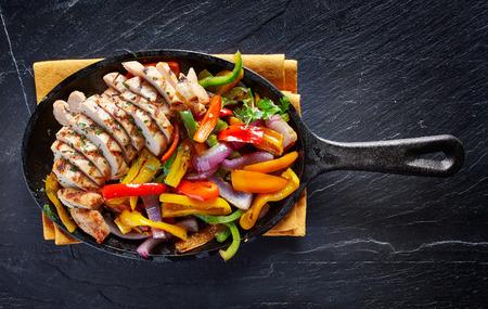 다크 슬레이트에 오버 헤드에서 철 프라이팬 샷 멕시코 구운 치킨 파 히타 스톡 콘텐츠