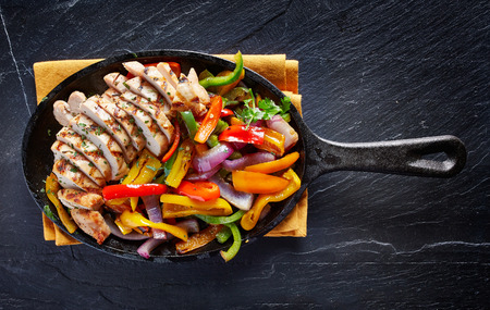 black dish: mexican grilled chicken fajitas in iron skillet shot from overhead on dark slate