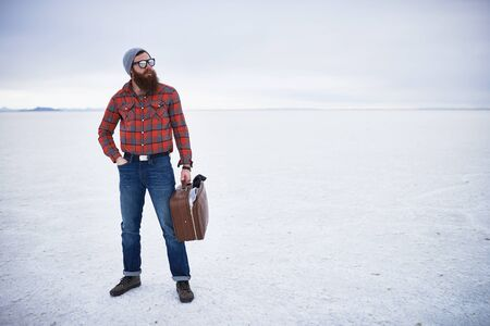 unconcerned: totally unconcerned lone traveling hipster standing with retro suitcase in vast empty salt flats Stock Photo