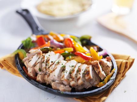 식탁 위에 흰색 치킨 파 히타 프라이팬