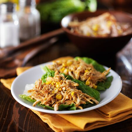 plate of two lettuce chicken wraps with spices and corn Stock Photo