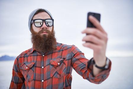 塩の平原でスマート フォンで selfies を取ってひげを生やしたヒップスター