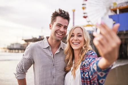 romantic couple: romantic couple taking selfie together on the beach in santa monica california Stock Photo