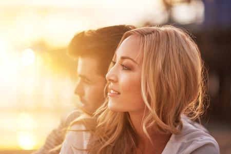 夕暮れ時のビーチで抱きしめるロマンチックなカップル