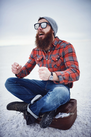 manly: hyped up hobo like hipster with manly awesome beard and sunglasses sitting on retro suicase in empty desolate salt flats