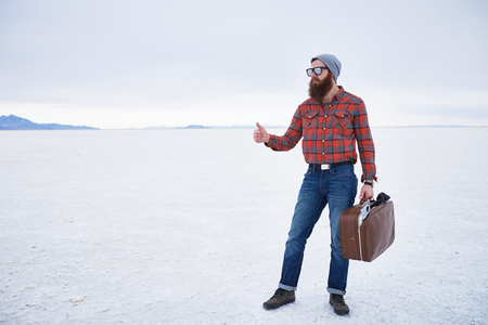 nonchalant: nonchalant entitled bearded hipster hitch hiker thumbing for a ride in empty vast salt flats with retro suitcase