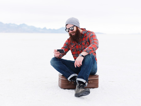 flannel: beard hipster with smart phone and suit case in the salt flats looking for directions