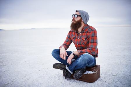 deep in thought: bearded hipster alone in the salt flats looking out in deep thought