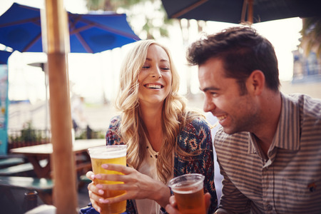 beer drinking: happy couple having a good time drinking beer together at outdoor pub or bar Stock Photo