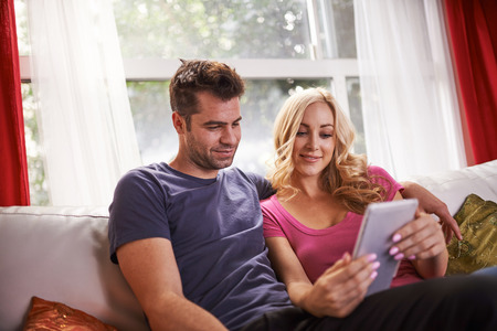 futon: lovely couple sitting on couch at home watching videos on tablet together
