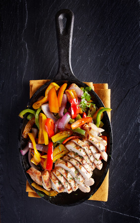 top down: grilled chicken mexican fajitas in iron skillet shot top down on dark slate