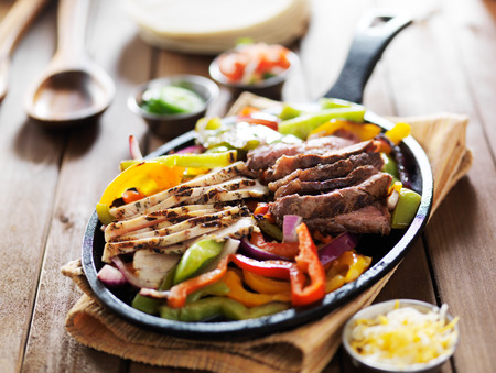 chicken and steak mexican fajitas in iron skillet