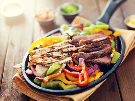 close up food: mexican food - skillet fajitas with steak and chicken on rustic wooden table