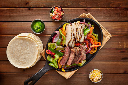 red hot iron: mexican steak and chicken fajitas in cast iron skillet shot top down with corn tortillas