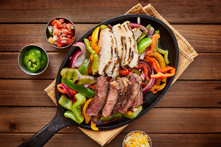 rustic fajita skillet meal with steak and chicken Stok Fotoğraf