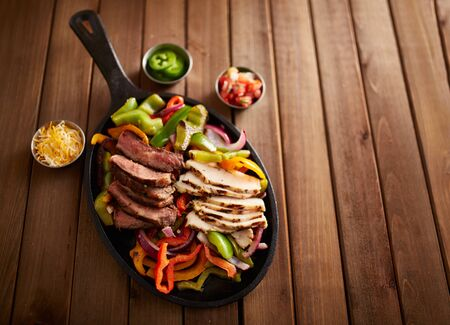 fajita: mexican steak and chicken fajitas in cast iron skillet shot with copy space composition