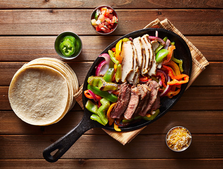 red hot iron: top down photo of mexican steak and chicken fajitas in iron skillet with corn tortillas Stock Photo