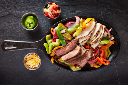 aerial view of a iron skillet filled with steak and chicken mexican fajitas on slate Stok Fotoğraf