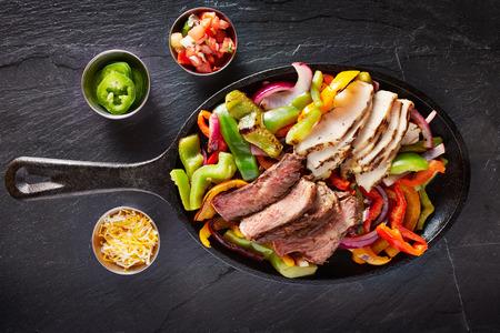 Luchtfoto van een ijzeren koekenpan gevuld met biefstuk en kip Mexicaanse fajitas op leisteen