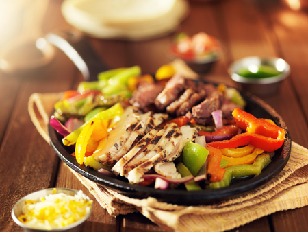 mexican steak and chicken fajitas in iron skillet with bell peppers and onion shot with warm colored light Stock Photo