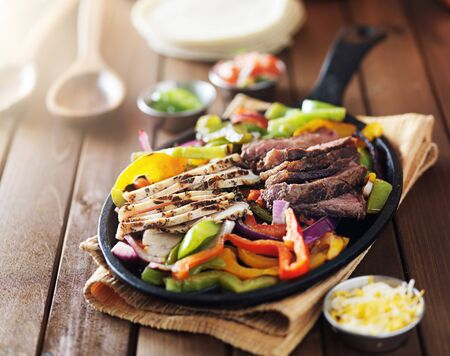 cast iron pan: freshly cooked spicy hot mexican steak and chicken fajitas in cast iron pan Stock Photo