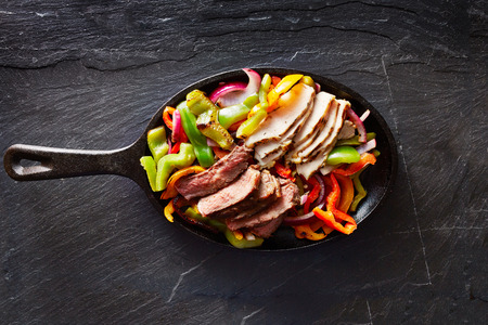 iron: mexican steak and chicken fajitas in cast iron skillet shot top down