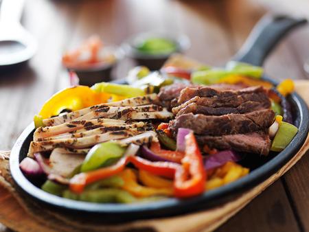 steak and chicken fajitas close up in cast iron fajita skillet Standard-Bild