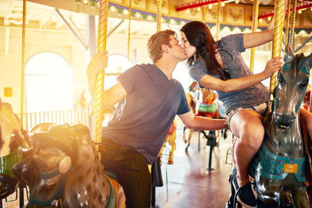 romantic couple kissing on merry go round