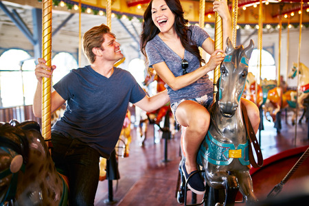 horse love horse kiss animal love: romantic couple on date having fun riding moving merry go round Stock Photo