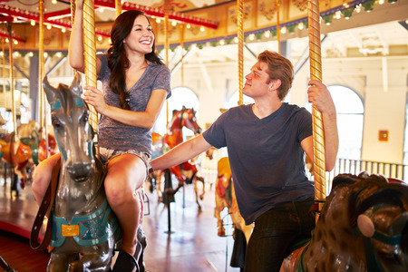 kiss love: romantic couple riding carousel together on date Stock Photo