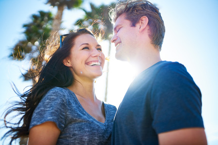 male hair: happy romantic couple outside on sunny day with palm trees Stock Photo